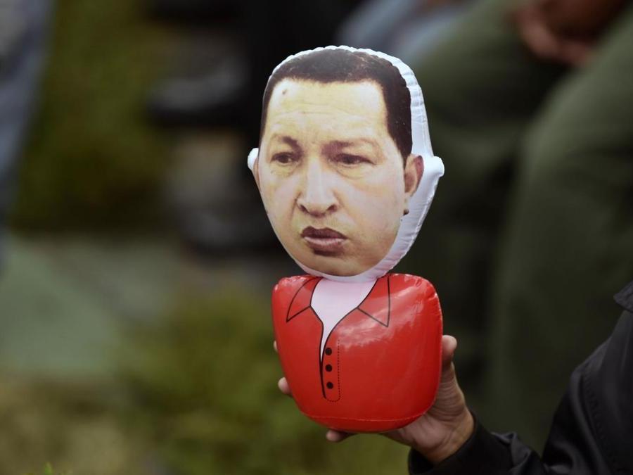 Un supporter di Maduro mostra un pupazzo con le sembianze del compianto Hugo Chavez (Photo by Luis ROBAYO / AFP)