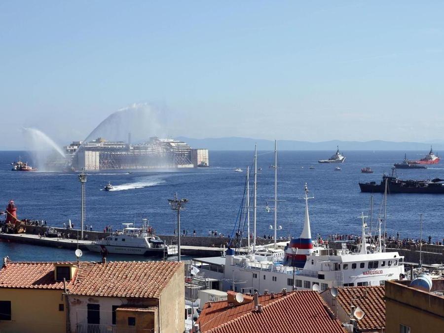 La nave Concordia durante le attivit?? preparatorie prima della partenza per l'ultimo viaggio a Genova, isola del Gilgio (Grosseto), 23 luglio 2014. ANSA/CLAUDIO GIOVANNINI