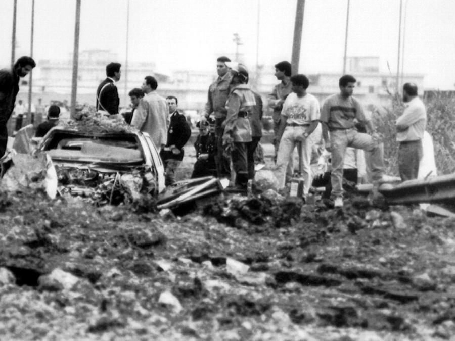 Gli investigatori sul luogo della strage del 23 maggio 1992, sull'autostrada A29, nei pressi dello svincolo di Capaci, a pochi chilometri da Palermo, dove morirono il magistrato antimafia Giovanni Falcone, sua moglie Francesca Morvillo e tre agenti della scorta, Vito Schifani, Rocco Dicillo, Antonio Montinaro. Gli unici sopravvissuti furono gli agenti Paolo Capuzza, Angelo Corbo, Gaspare Cervello e l'autista giudiziario Giuseppe Costanza (ANSA)