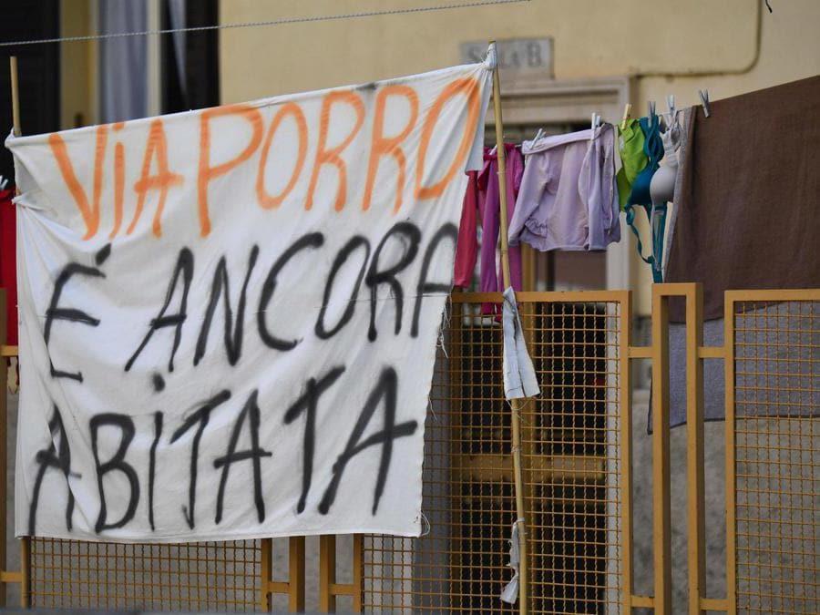 Un lenzuolo con la scritta ''via Porro è ancora abitata'' durante le operazioni per far entrare gli sfollati di via Porro nelle loro case per l'ultima volta, per poter recuperare le ultime cose, Genova. ANSA/LUCA ZENNARO