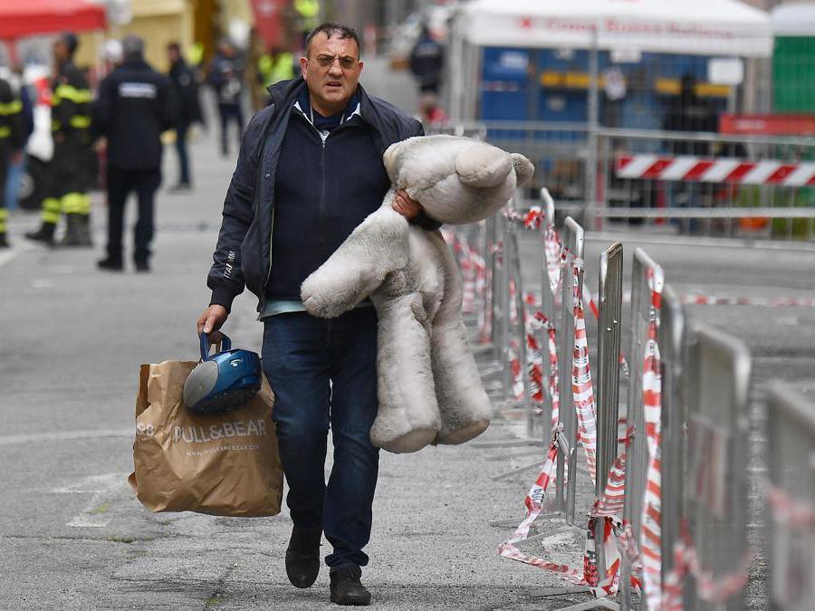 Uno sfollato trasporta un orso appartenuto ai suoi figli nel giorno della ripresa delle operazioni per consentire agli sfollati di entrare nelle loro case per l'ultima volta, per poter recuperare le ultime cose, Genova. ANSA/LUCA ZENNARO