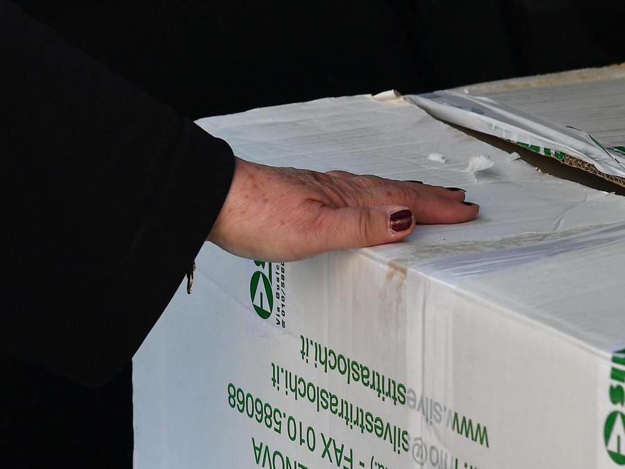 La mano di una signora sfollata tiene la scatola con le sue cose recuperate e stipate in auto. Genova. ANSA/LUCA ZENNARO