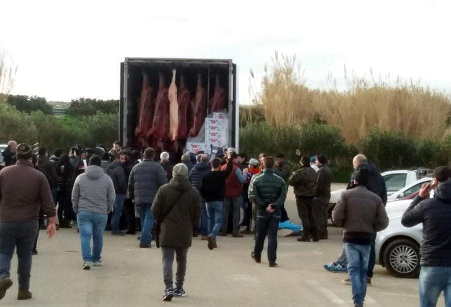 """La protesta dei pastori sardi per il crollo del prezzo del latte arriva nello scalo di Porto Torres (Sassari). Oltre un centinaio di contestatori ha fermato i tir frigo imbarcati a Genova. Gli allevatori hanno fermato un mezzo che trasportava carni suine provenienti dalla Francia e hanno gettato gran parte del carico a terra, chiedendo l'intervento delle autorità sanitarie e denunciando """"le pessime condizioni della merce destinata al mercato locale"""". ANSA/FOIS"""
