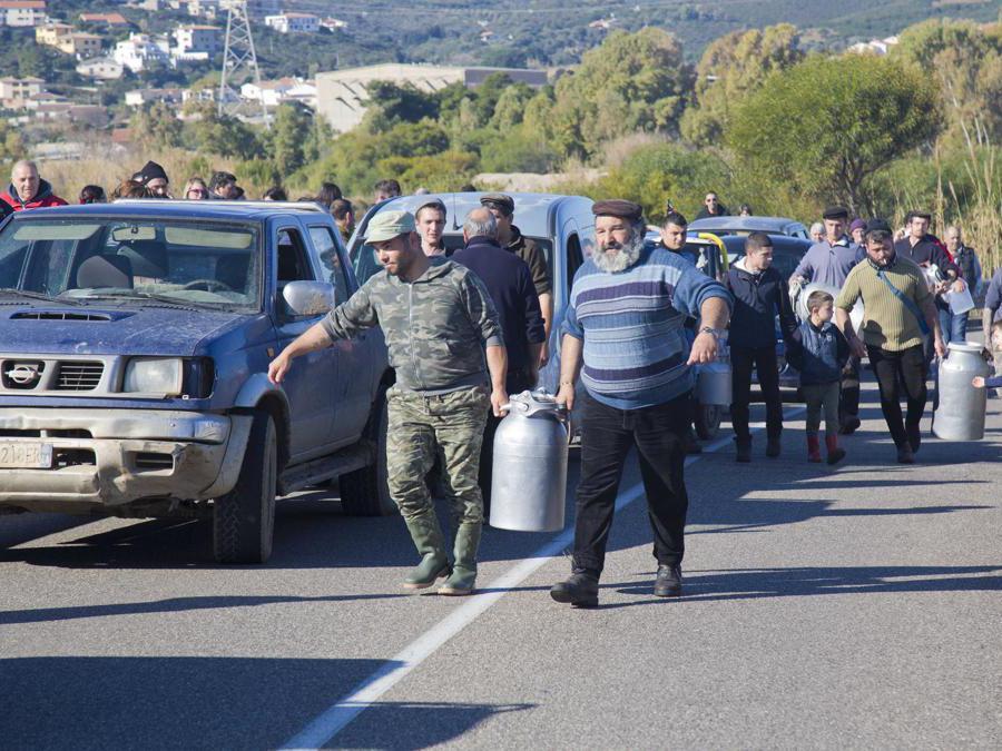 Alcuni pastori versano sulla strada il latte bloccando il traffico. Foto Italy Photo Press/Fabo Murru