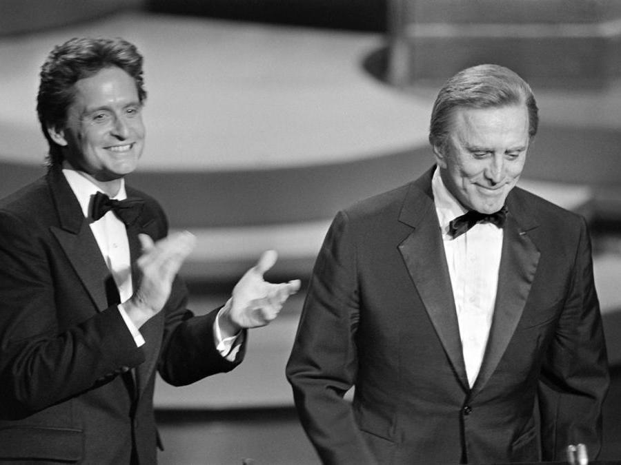 In questa foto  scattata il 25 marzo 1985, l'attore statunitense Michael Douglas (sinistra) applaude suo padre l'attore statunitense Kirk Douglas durante la 57a edizione degli Academy Awards, a Hollywood, in California. (Photo by ROB BOREN / AFP)
