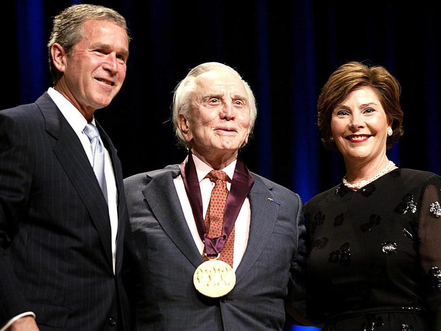 Foto  scattata il 22 aprile 2002. Il presidente degli Stati Uniti George W. Bush  e la First Lady Laura Bush  con l'attore Kirk Douglas. Washington. (Photo by STEPHEN JAFFE / AFP)