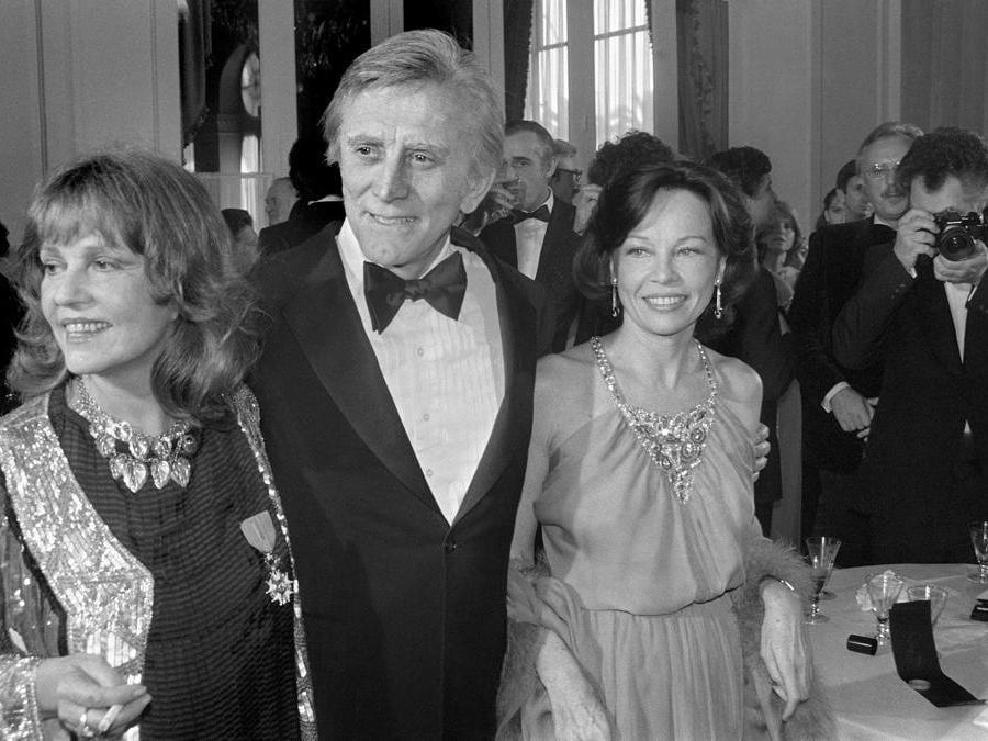 In questa foto del file scattata il 9 maggio 1980, l'attore statunitense Kirk Douglas è accompagnato dalle attrici francesi Jeanne Moreau (sinistra) e Leslie Caron, durante il Festival Internazionale del Cinema di Cannes. (Photo by RALPH GATTI / AFP)