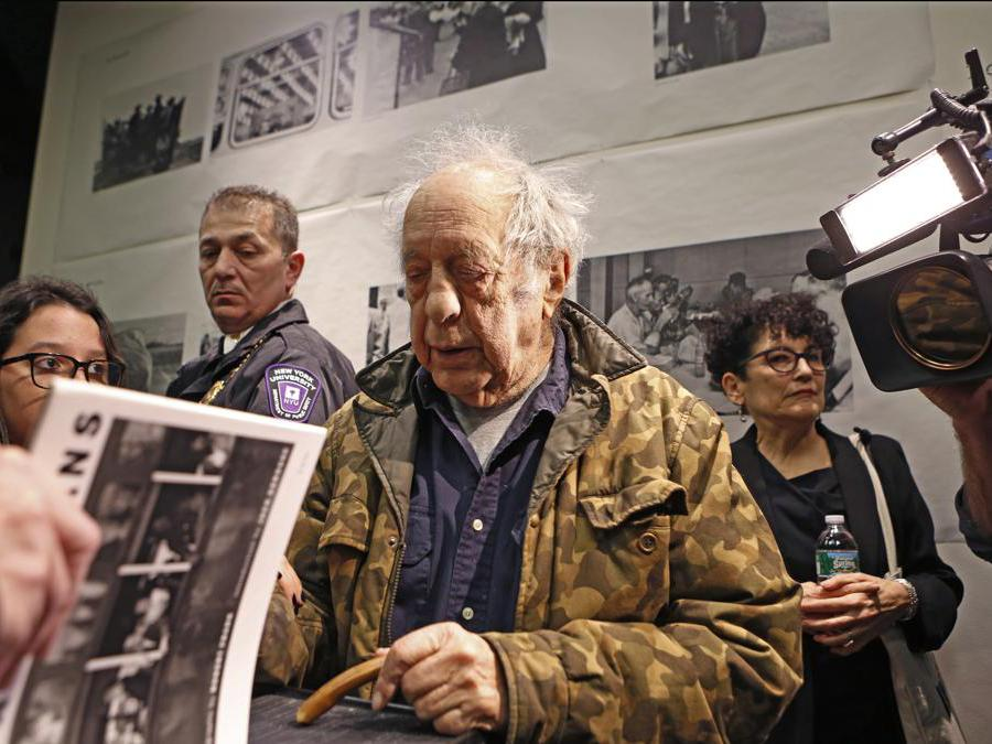 Robert Frank alla New York University's Tisch School of the Arts, nel 2016, mentre autografa una copia di The Americans (AP Photo/Kathy Willens)
