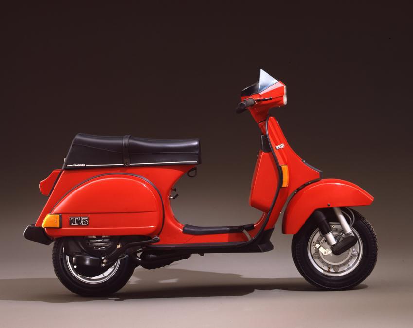 """Vespa T 5 Pole Position (1985) - Anche la serie PX trova, con la T 5, il modello """"supersportivo"""". Nuovo il motore, con cilindro in alluminio a 5 travasi; ma nuovo anche il design: uno spoiler arricchisce lo scudo"""