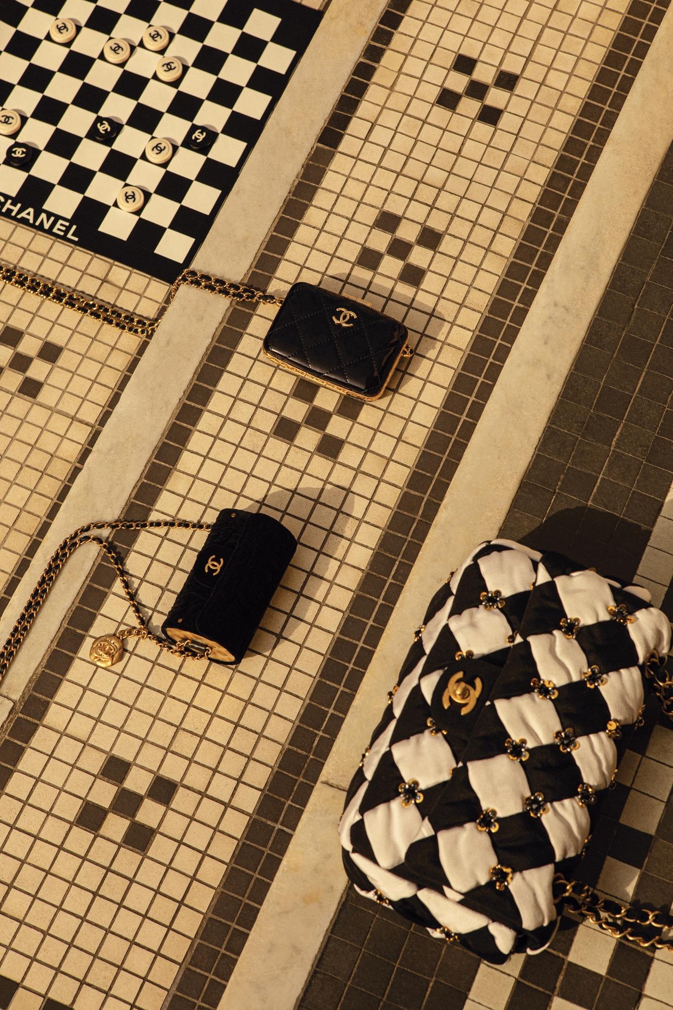 Mini tracolle con catena, in vernice (2.020 €) e velluto(2.020 €), borsa in seta ricamata e trapuntata(9.180 €), scacchiera arrotolabile (5.000 €). Tutto CHANEL. Tutte le immagini della gallery sono di Kenny Whittle.