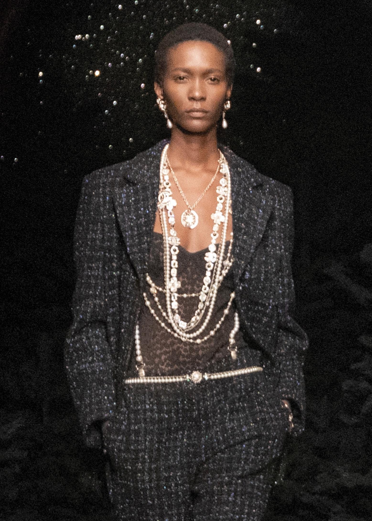 Chanel. Body in pizzo nero con giacca e pantaloni in tweed iridescente. Collane in metallo effetto dorato con maxi charm e multifilo in perle.