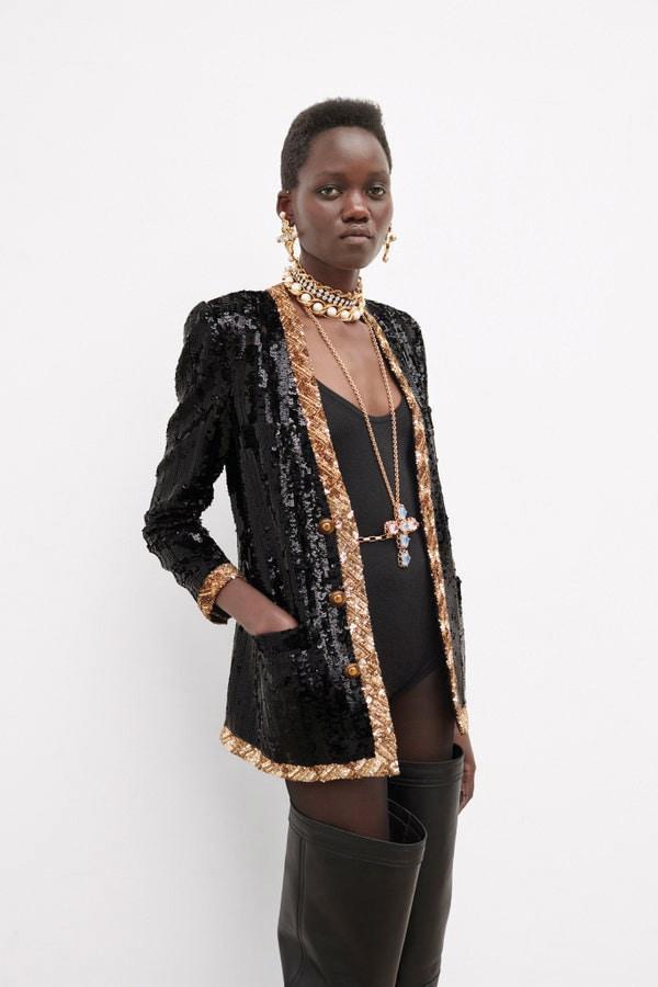 Saint Laurent by Anthony Vaccarello. Cardigan in paillettes bicolore, chocker con catene e perle, pendente e orecchini a croce in metallo e cristalli.