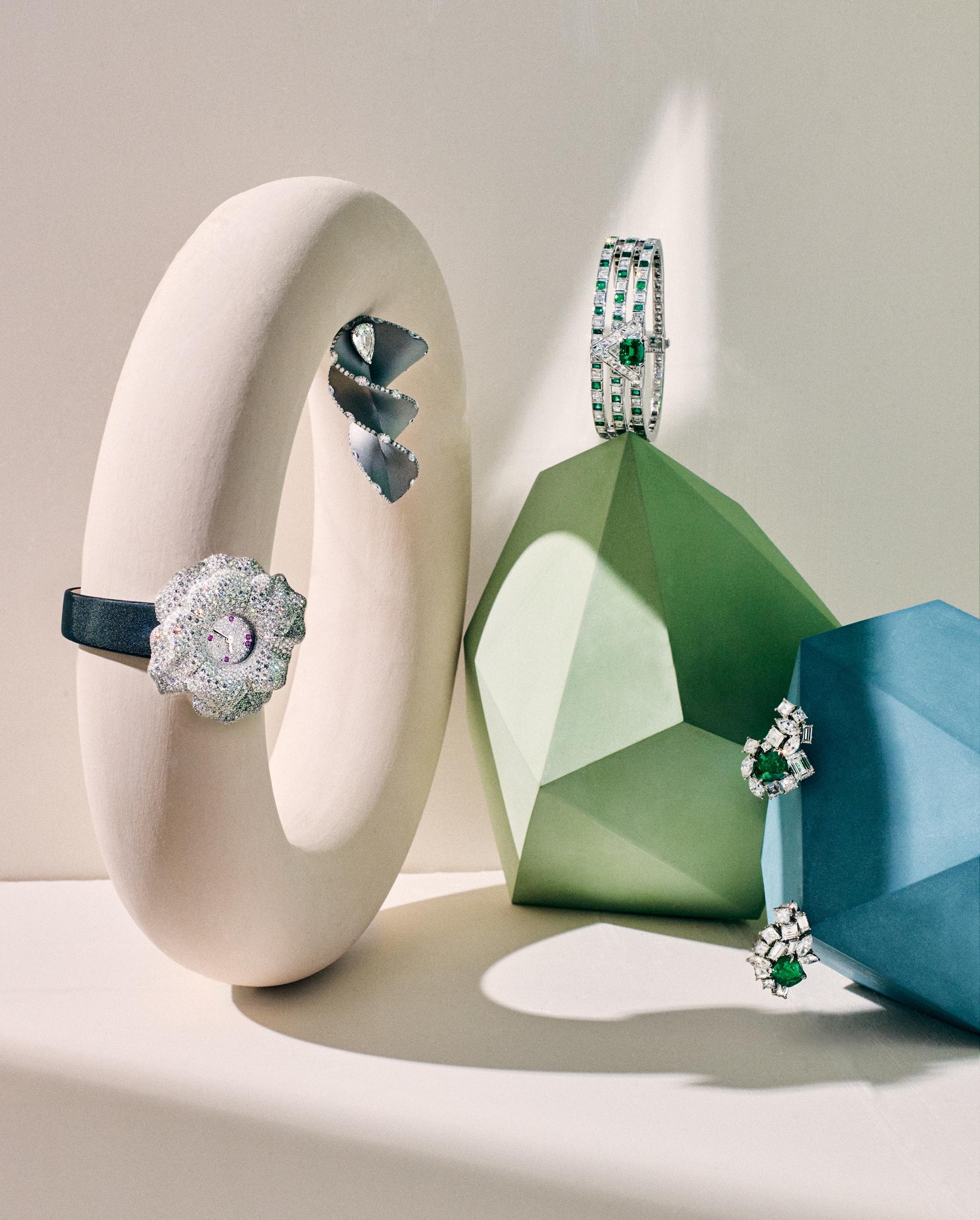 Da sinistra, orologio La Rose, in oro bianco incastonato con pavé di diamanti e zaffiri rosa, JAEGER-LECOULTRE. Orecchino a spirale in titanio, oro bianco e diamanti, FABIO SALINI. Bracciale rigido  a damier di brillanti e smeraldi su oro bianco, LOUIS VUITTON. Orecchini asimmetrici, in platino, con smeraldo centrale e diamanti, DIOR JOAILLERIE. In tutta la gallery, sculture in ceramica della collezione Polyèdres, PIA VAN PETEGHEM.