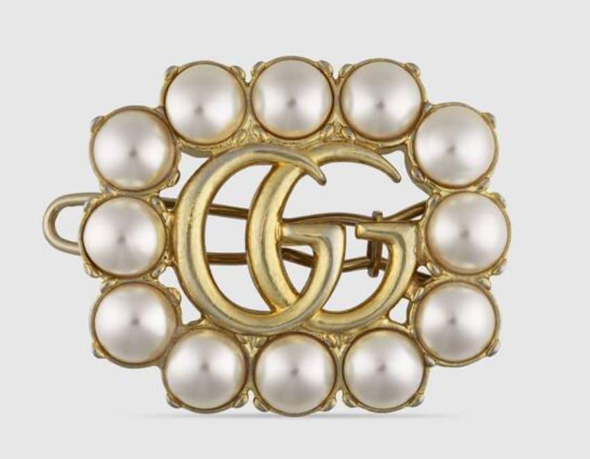 GUCCI Fermaglio per capelli con doppia G in metallo anticato bronzo e cornice di perle, (350 euro).