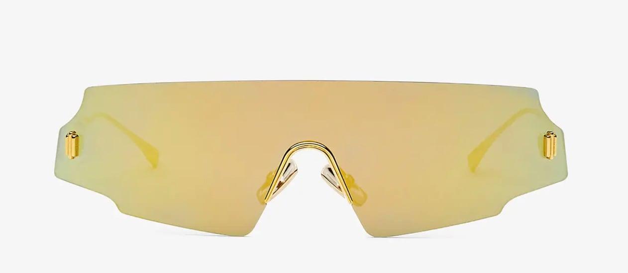 FENDI Mascherina con dettagli in metallo diamantato e lente unica specchiata color oro giallo, modello Forcefull presentato nella sfilata AI20/21 (360 euro).