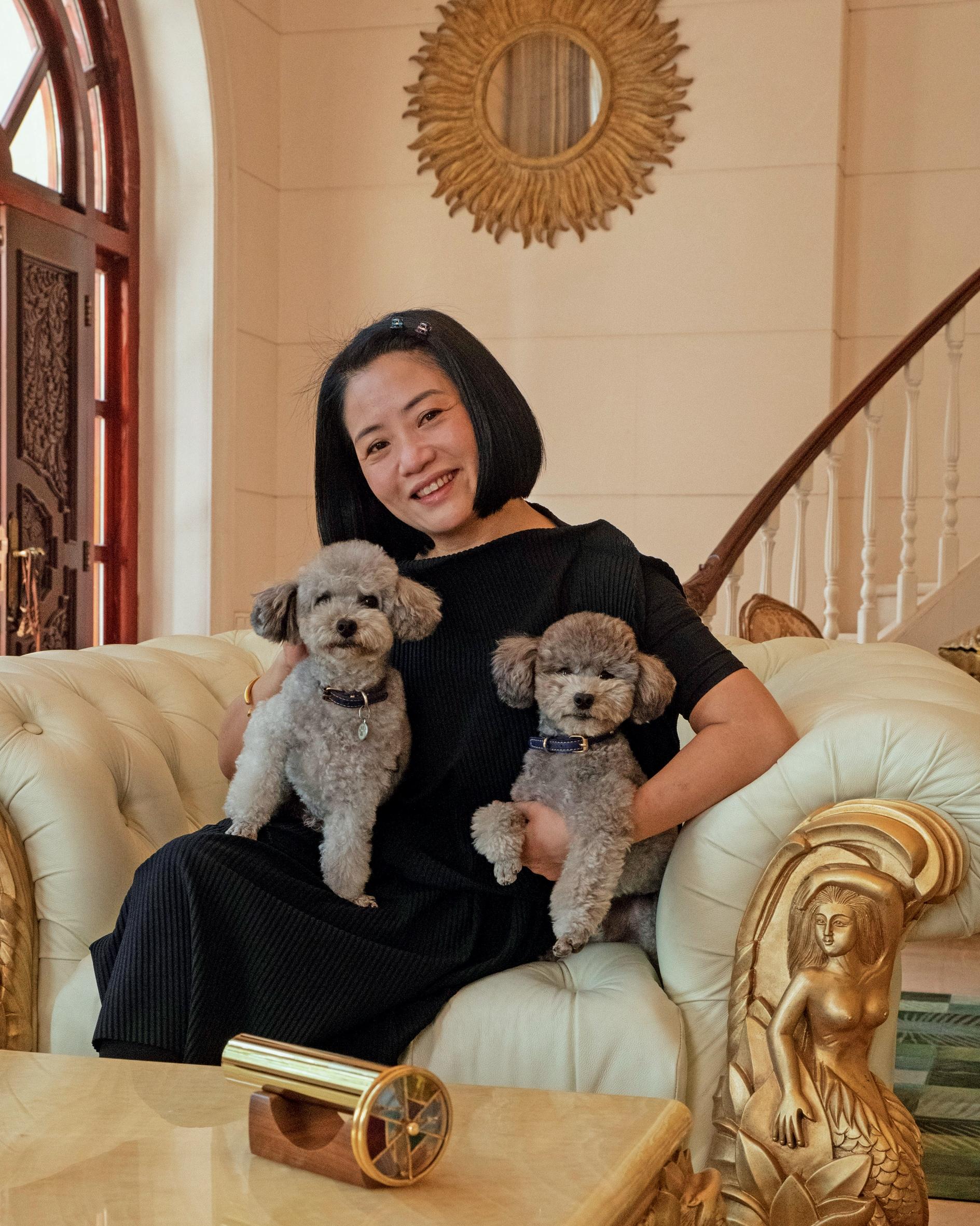 """La stilista Guo Pei nella sua casa di Pechino con i barboncini Nuomi (""""riso appiccicoso"""") e Zhuanzhuan."""
