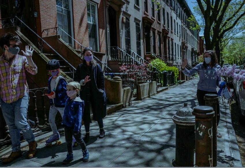 """Laura Giromini saluta una famiglia di vicini di casa che passeggiano indossando le mascherine che lei gli ha donato e che realizza durante la """"pausa"""" - così è chiamato il lockdown newyorkese - ricevendo in cambio fiori o altra stoffa."""