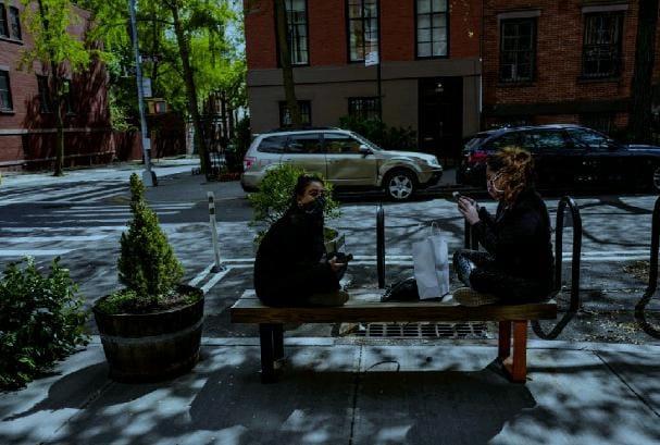 Due amiche si trovano nel tardo pomeriggio sedute ai poli opposti di una panchina onde mantenere la distanza di sicurezza