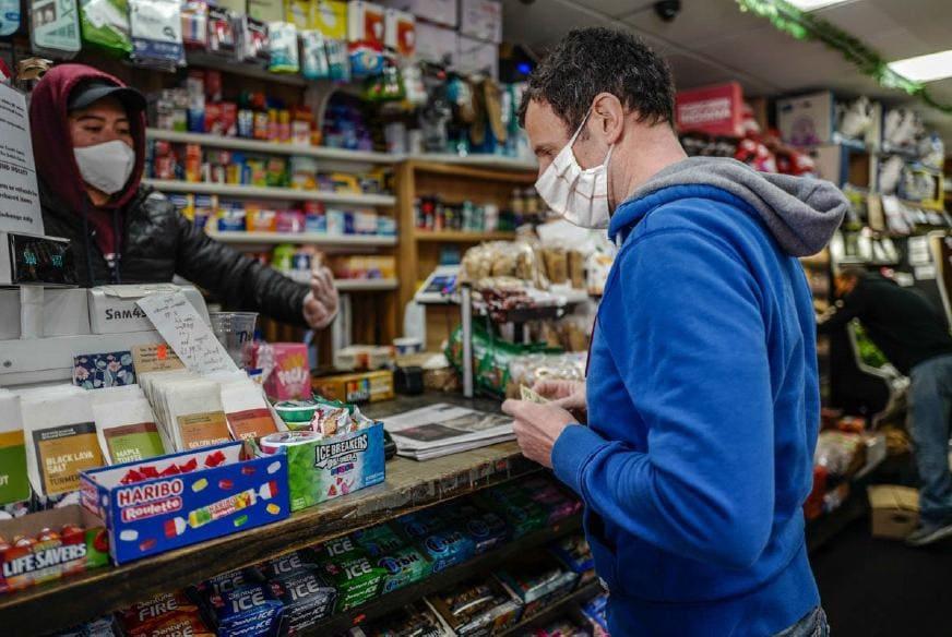 """Luca Arrigoni compra il giornale e dei biscotti al """"deli"""" sottocasa, l'equivalente italiano dell'alimentari di quartiere."""