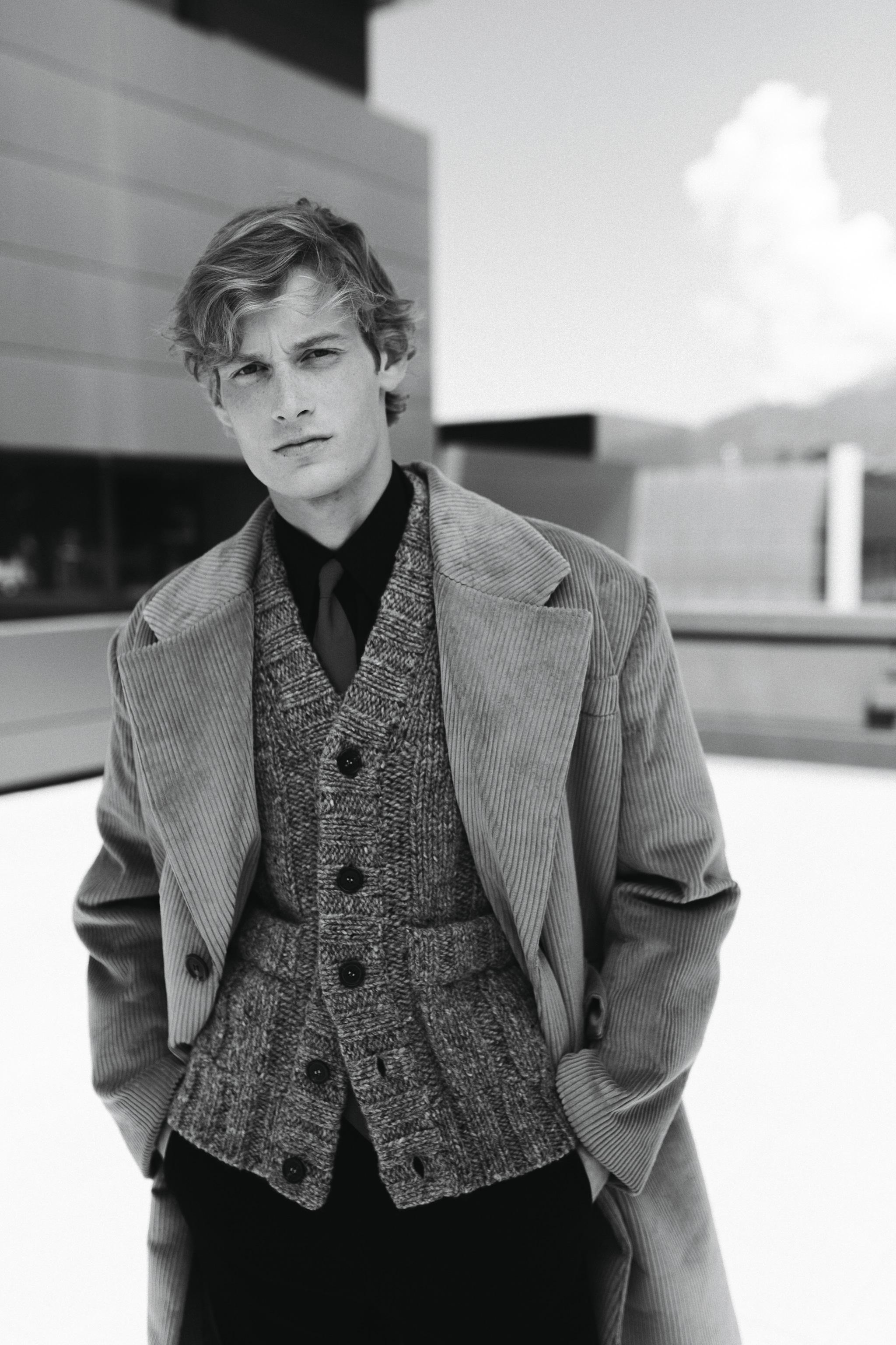 Cappotto oversize in velluto a coste, cardigan gilet in lana con tasche applicate, cravatta in seta e camicia in cotone, pantaloni in fresco lana, Prada.