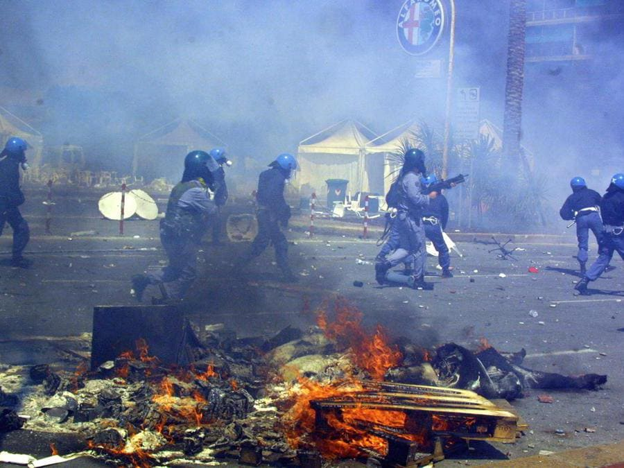 Police passes by burning debris following clashes with anti-globalisation protest against the G8 summit in Genoa 21 July 2001. AFP PHOTO GABRIEL BOUYS (Photo by GABRIEL BOUYS / AFP)