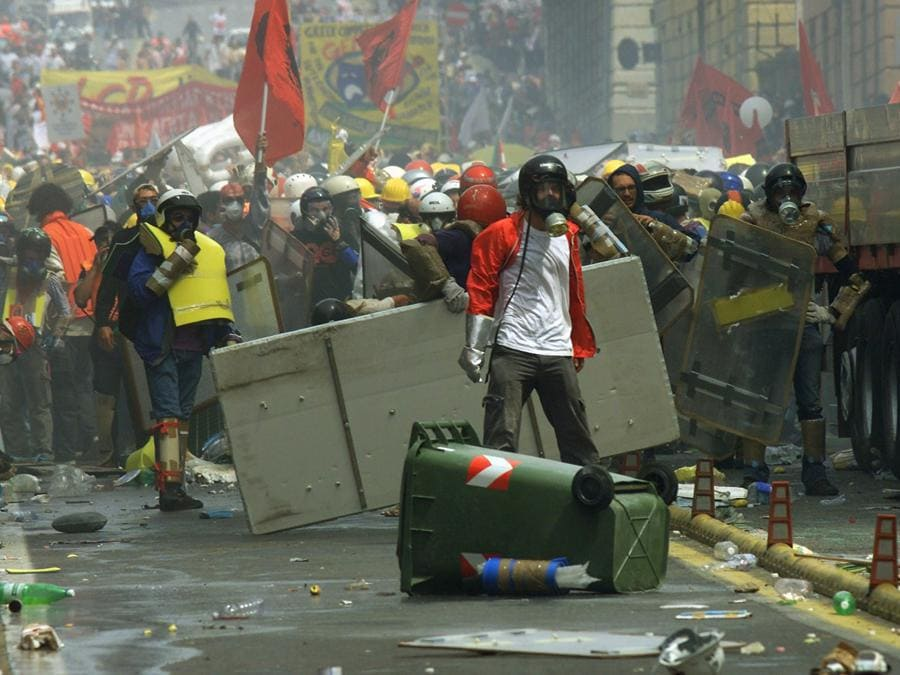 Anti-globalization protesters wearing makeshift protective clothing block a street during clashes with police in downtown Genoa July 20, 2001. Police have been expecting violence as some 150,000 anti-globalization protesters take to the streets in demonstrations while the G8 summit takes place here in Genoa. DJM/CRB (Reuters)
