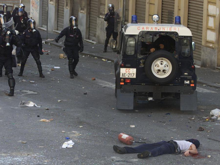 A Carabinieri vehicle speeds away after reversing over dead protester Carlo Giuliani who had been shot twice by the officers inside during rioting in central Genoa July 20, 2001. Police fired live rounds, tear gas and used water cannon in an attempt to disperse the thousands of protestors who are demonstrating against the G8 summit. REUTERS/Dylan Martinez (ITALY)