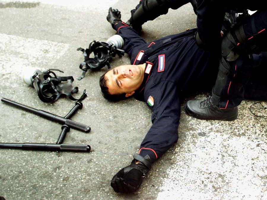 A policeman lies injured on the ground following clashes with anti-globalization protesters taking place thoughout Genoa, July 20, 2001. Police have faced violence from some of the estimated 150,000 anti-globalization protesters who have taken to the streets in demonstrations while the G8 summit takes place here in Genoa. DJM (Reuters)