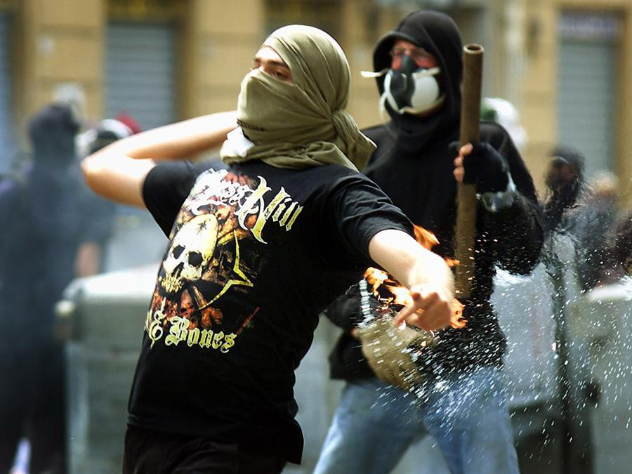 Anti-globalization protesters throw petrol bombs at police as wide spread fighting errupted thoughout Genoa July 20, 2001. Police have been expecting violence as some 150,000 anti-globalization protesters take to the streets in demonstrations while the G8 summit takes place here in Genoa. DJM (Reuters)