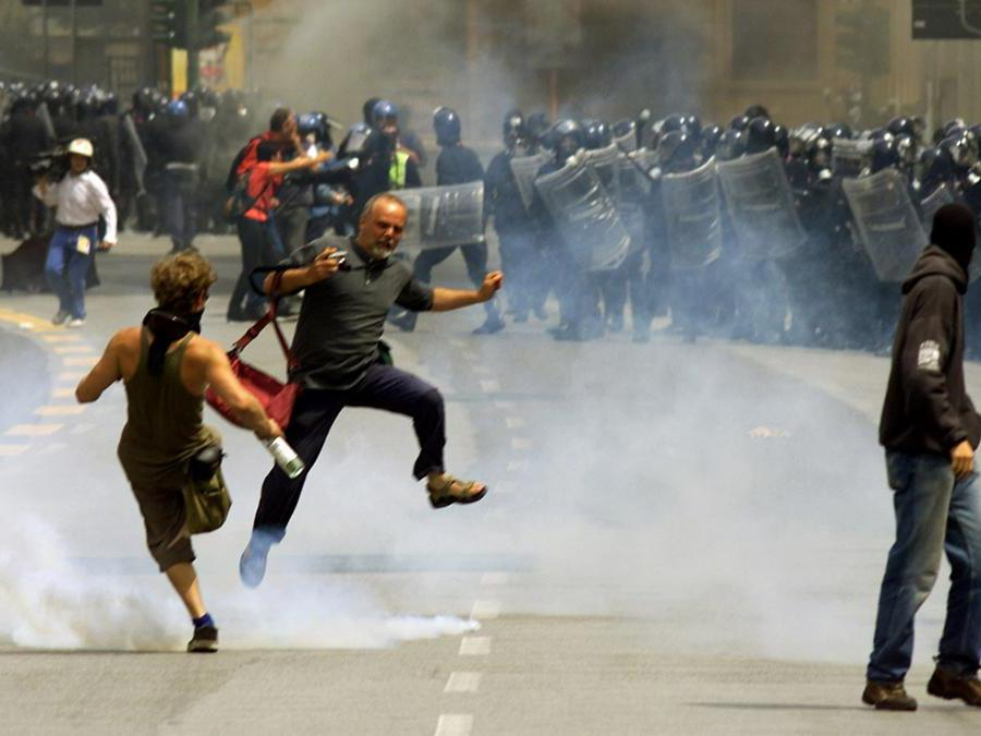 Anti-globalization protesters attempt to dodge tear gas fired at them during clashes with police in downtown Genoa July 20, 2001. Police have been expecting violence as some 150,000 anti-globalization protestors take to the streets in demonstrations while the G8 summit takes place here in Genoa. DJM/CRB (Reuters)