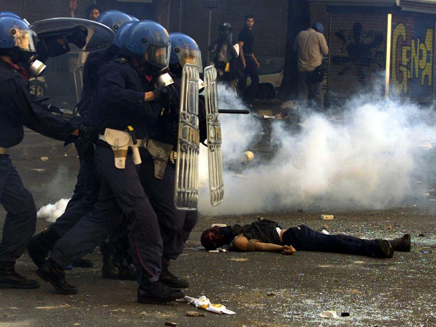 Riot police storm past dead protester Carlo Giuliani who has been shot and killed by Carabiniere during rioting in central Genoa July 20, 2001. Police fired live rounds, tear gas and used water cannon in an attempt to disperse the thousands of protestors who are demonstrating against the G8 summit. REUTERS/Dylan Martinez (ITALY) For best quality see GF2DRXALGYAB RUS/CRB