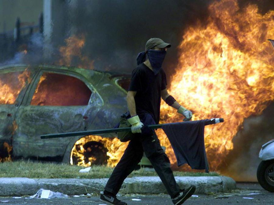 An anti-globalization protester strolls past a burning car as widespread clashes with police erupted thoughout Genoa July 20, 2001. Police have been expecting violence as some 150,000 anti-globalization protesters take to the streets in demonstrations while the G8 summit takes place here in Genoa. (Reuters)