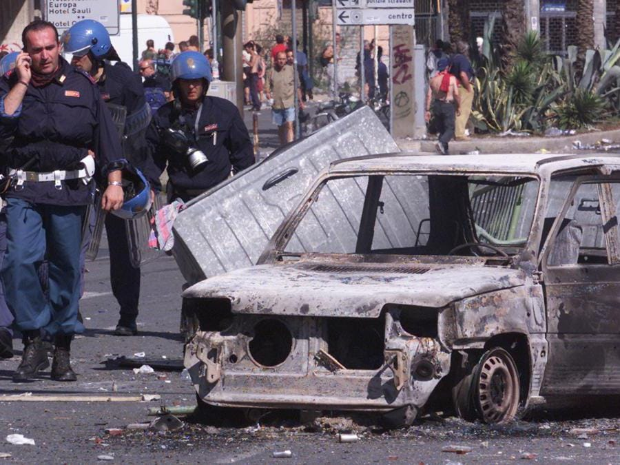 A policeman talks on the telephone as he walks past a burned out car during a second day of rioting in central Genoa, July 21, 2001. The G8 leaders continued with their summit dismissing calls to cancel it after police shot dead an Italian protester during violent anti-capitalist unrest on its opening day. RUS/CLH/ (Reuters)