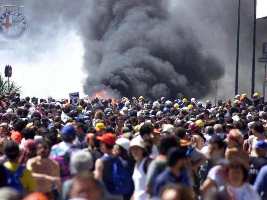 Thick smoke rises over the crowd as riot police clash with the demonstrators in the center of the Genoa July 21, 2001. Italian police and anti-capitalist protesters clashed on Saturday on the third day of protests in the Mediterranean city hosting the Group of Eight big power summit. (Reuters)