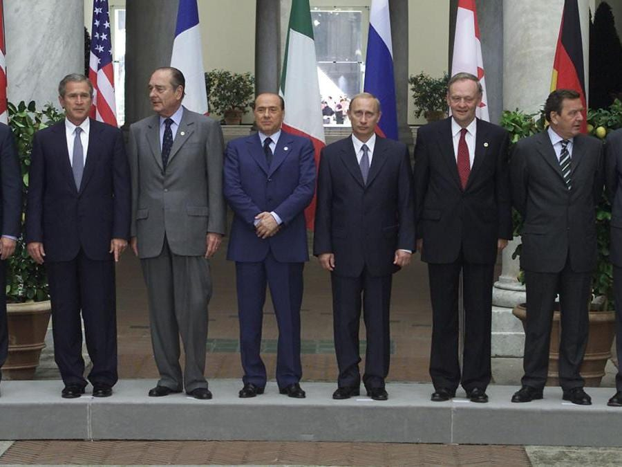 The leaders of the G8 nations stand on a podium as they pose for a family picture at the end of the summit in central Genoa, July 22, 2001. They are (L to R) Japan's Prime Minister Junichiro Koizumi, Britain's Prime Minister Tony Blair, US President George W. Bush, French President Jacques Chirac, Italian Prime Minister Silvio Berlusconi, Russian President Vladimir Putin, Canadian Prime Minister Jean Chretien and German Chancellor Gerhard Schroeder. Also with them are representatives from the Europe, Belgium Prime Minister Guy Verhofstadt and President of the European Commission Romanao Prodi. RUS/GB (Reuters)