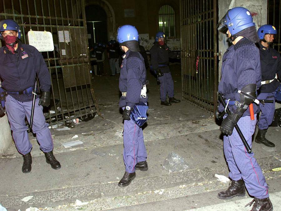 Agenti di polizia davanti al cancello della scuola Diaz di Genova il 21 luglio 2001. ANSA / LUCA ZENNARO