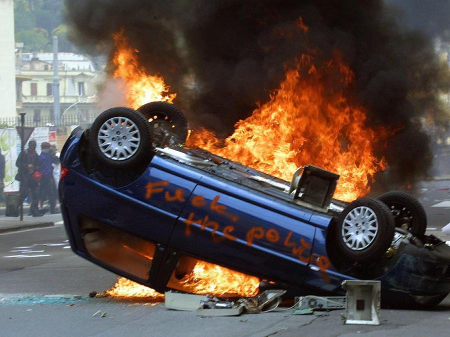 """GEN12-20010720-GENOA, ITALY: An overturned car is set on fire Friday 20 July 2001, by anti-globalisation protesters demonstrating in Genoa. Hardline demonstrators have vowed to try to break into the high-security """" red zone """" surrounding the Palazzo Ducale, where the leaders of the G8 (Group of Eight) started their three-day annual summit Friday. ANSA-EPA PHOTO/ANJA NIEDRINGHAUS/hhCD"""