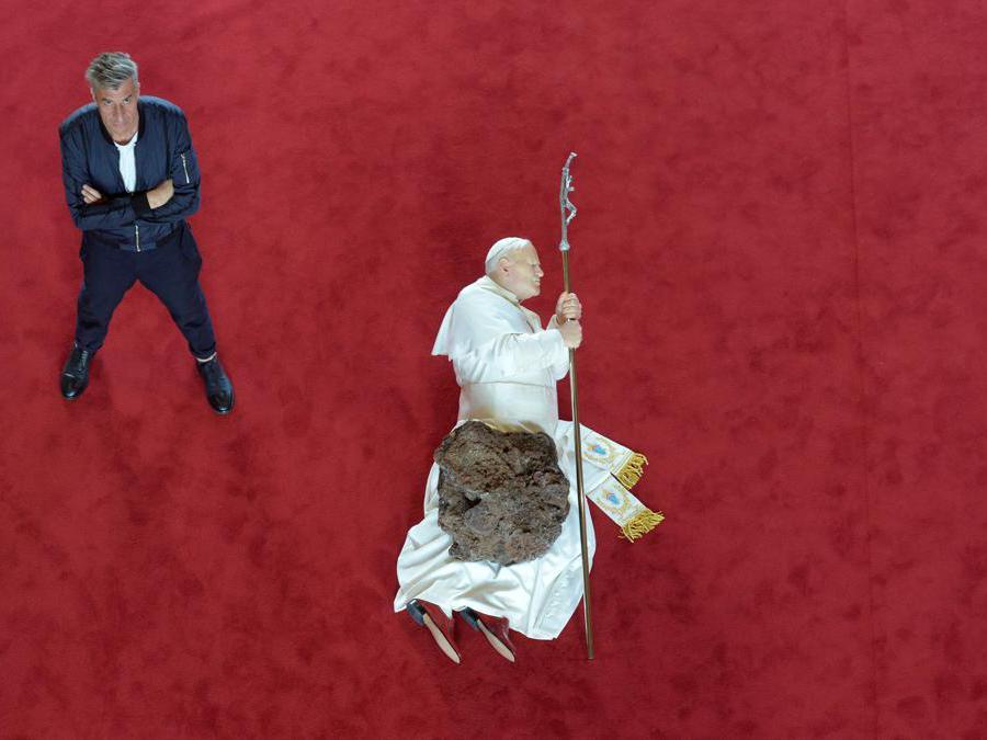 """Maurizio Cattelan posa accanto alla sua scultura raffigurante papa Giovanni Paolo II """"La Nona Ora"""" (Photo by ALAIN JOCARD / AFP)"""