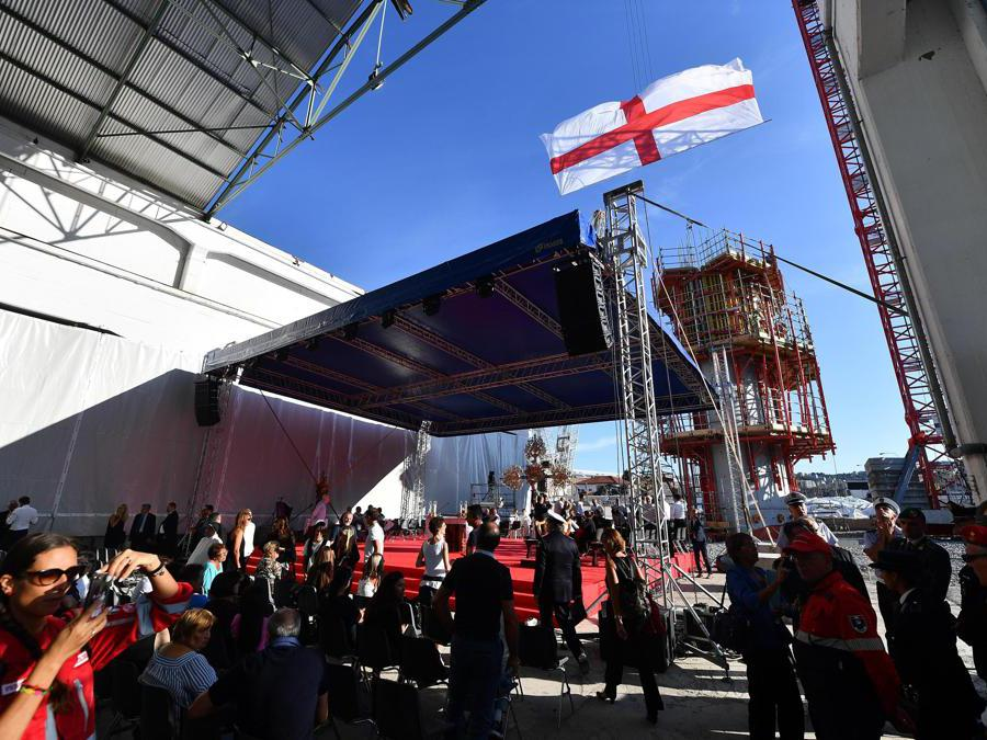 Una bandiera di San Giorgio, simbolo di Genova, viene sventolata mentre la gente si riunisce per assistere alla cerimonia commemorativa per le vittime del crollo del ponte Morandi a Genova (Luca Zennaro/Ansa)