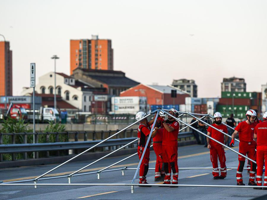 I volontari della Croce Rossa  allestiscono una grande tenda per ospitare le persone prima della cerimonia ufficiale in occasione del primo anniversario del crollo del ponte  Morandi (Simone Arveda/Ansa)
