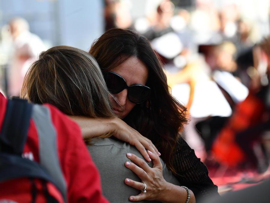 I parenti delle vittime si abbracciano mentre si riuniscono per la cerimonia ufficiale nel primo anniversario del crollo del ponte  Morandi, (Luca Zennaro/Ansa)