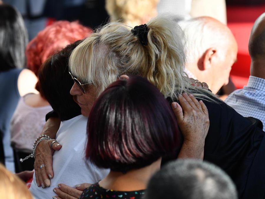 I parenti delle vittime si abbracciano mentre si riuniscono per la cerimonia ufficiale nel primo anniversario del crollo del ponte  Morandi (Luca Zennaro/Ansa)