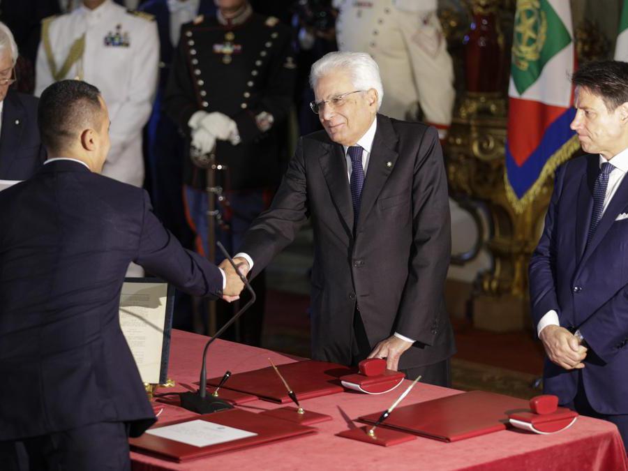 Il ministro degli Esteri Luigi Di Maio, a sinistra, stringe la mano al presidente  Sergio Mattarella, al centro, mentre il Primo Ministro Giuseppe Conte osserva. (AP Photo/Andrew Medichini)