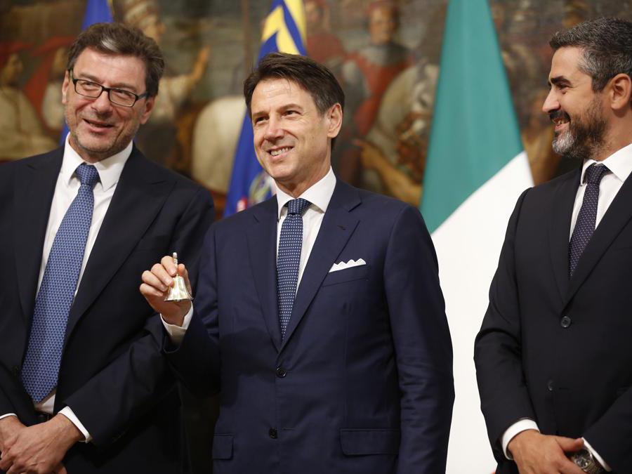 Il primo ministro  Giuseppe Conte, affiancato dal nuovo sottosegretario di Stato Riccardo Fraccaro, a destra, e dal sottosegretario uscente Giancarlo Giorgetti. (AP Photo/Domenico Stinellis)