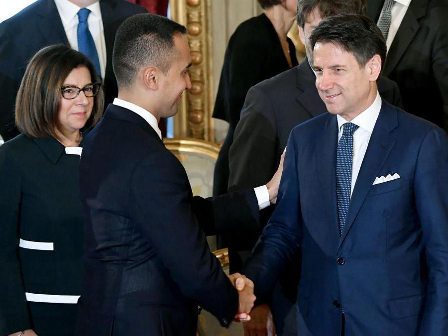 Il Ministro degli Esteri  Luigi Di Maio (centro) stringe la mano al Primo Ministro  Giuseppe Conte (destra) sotto lo sguardo del Ministro delle Infrastrutture e dei trasporti  Paola De Micheli.  (Photo by Andreas SOLARO / AFP)