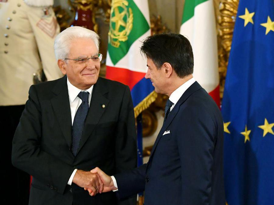 Il presidente della Repubblica Sergio Mattarella (sinistra) e il primo ministro  Giuseppe Conte si stringono la mano durante la cerimonia del giuramento al palazzo del Quirinale. (Photo by Andreas SOLARO / AFP)