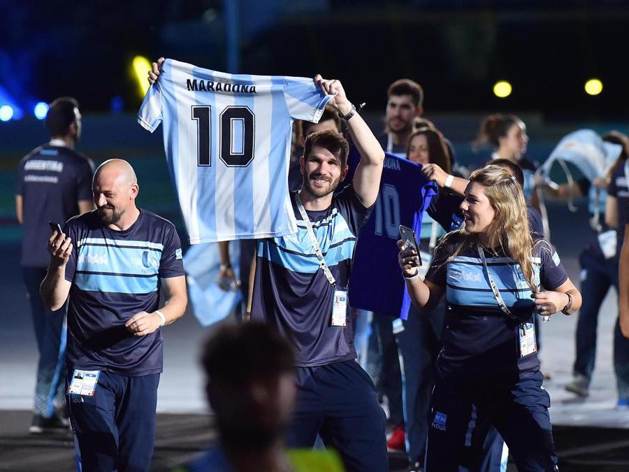 Gli atleti della delegazione argentina sfilano mostrando una maglia di Maradona (Italy Photo Press)
