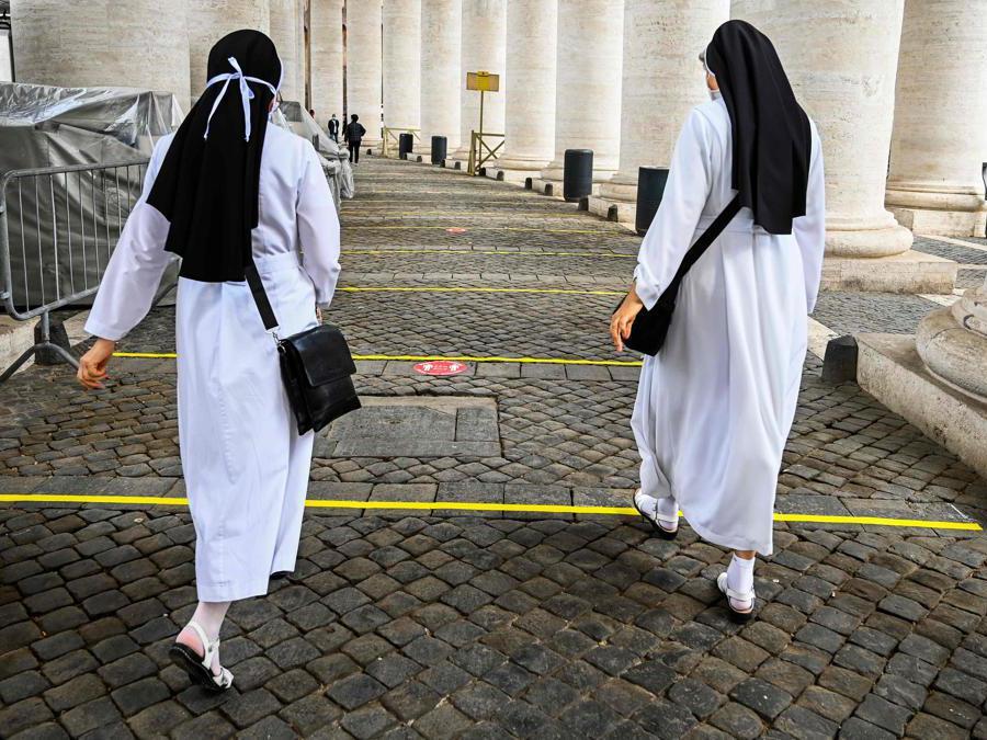 Due suore attraversano l'aera di sicurezza per accedere alla Basilica di Piazza San Pietro (Photo by Vincenzo Pinto / AFP)