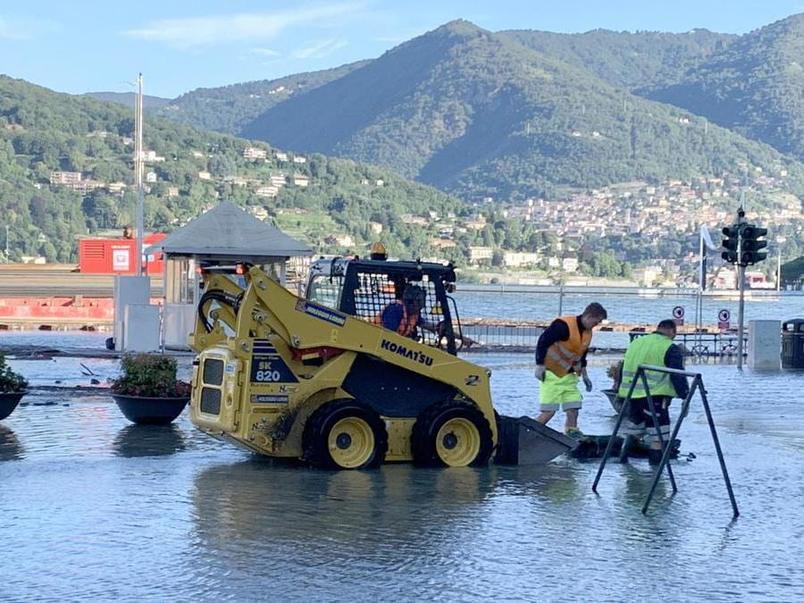Operai al lavoro in piazza Cavour a Como ricoperta di acqua e detriti esondati dal lago a causa delle copiose piogge. (Ansa / Maatteo Bazzi)