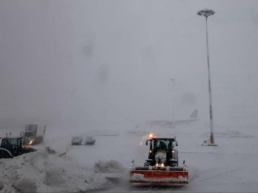 Mezzi meccanici tolgono la neve sulla pista dell'aeroporto di Linate, 28 dicembre 2020. (Ansa / Sara Bonifazio)